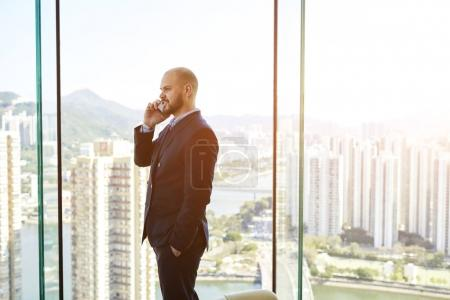 Male CEO  is standing in his office near window with view of business district background with copy space
