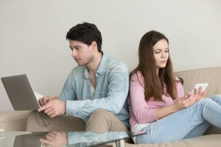Young couple sitting back to back using laptop computer, tablet