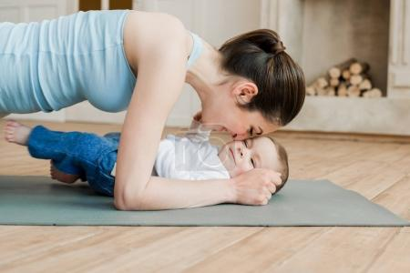 Mother doing plank exercise with her son