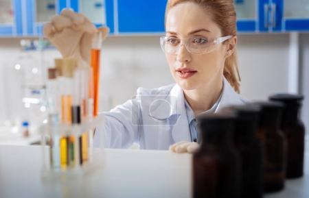 Attentive female person examining orange liquid