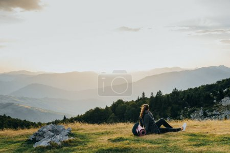 Young woman hiker enjoy the beautiful landscape at mountain peak