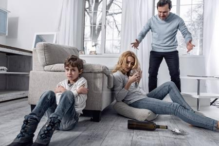 Scared boy crying while an angry father quarreling with his alcoholic wife