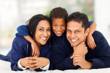 little indian boy hugging his parents on bed