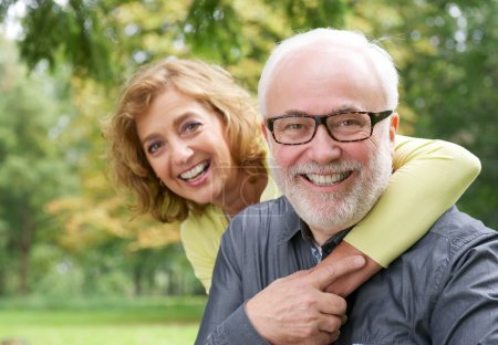 Happy older woman embracing smiling older man