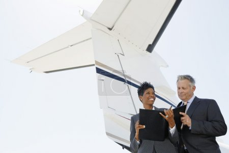 Business people below wing of private jet