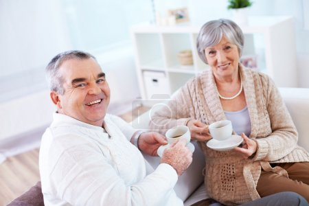 Mature man and his wife drinking tea