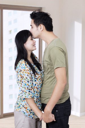 Husband kissing his wife in a new home