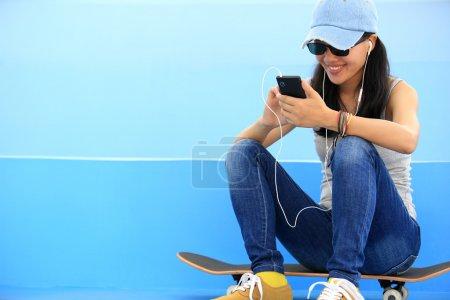 Woman skateboarder listening music