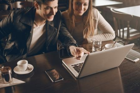 Couple at the bar using a laptop