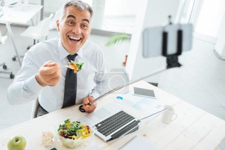 Businessman taking selfies during his lunch break